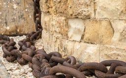 Una catena enorme, vecchia ed arrugginita che pende giù dalla parete dell'arenaria a St Elmo forte, La Valletta, Malta fotografia stock libera da diritti
