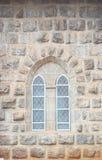 Una cattedrale ha modellato la finestra in una vecchia parete pietrosa di un monumento storico Fotografie Stock Libere da Diritti