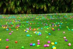 Una caza del huevo de Pascua con los huevos plásticos en un césped verde