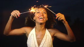 Una celebración sonriente hermosa de la mujer joven con la bengala en la noche en la cámara lenta