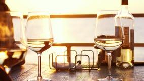 Una cena romántica en verano en una playa en la puesta del sol con dos vidrios del vino blanco y de una botella del vino Foto de archivo libre de regalías
