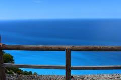 Una cerca de madera con un mar azul en el fondo fotos de archivo libres de regalías