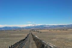 Una cerca del rancho que lleva a las montañas rocosas foto de archivo