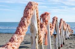 Una cerca hecha de registros de madera y la cuerda rope en la arena en el muelle en la 'promenade' de la playa cerca del mar en I Imagenes de archivo