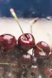 Una cereza dulce madura brillante miente detrás de un vidrio mojado con descensos que fluyen del agua Imagenes de archivo