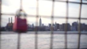 Una cerradura del amor cuelga en una cerca de cadena contra el paisaje urbano de NYC metrajes