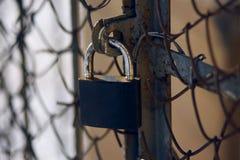 Una cerradura gastada que cubre una vieja puerta oxidada con una malla metálica foto de archivo libre de regalías