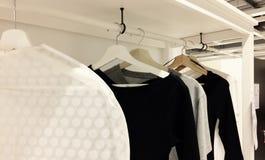 Una certa varietà di vestiti che appendono nel centro commerciale con varietà immagine stock