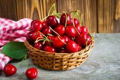 Una cesta con los cherrys en la tabla de madera Fotografía de archivo
