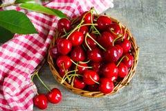 Una cesta con los cherrys en la tabla de madera Fotografía de archivo libre de regalías