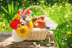Una cesta con los pasteles y las flores en el jardín Imagenes de archivo