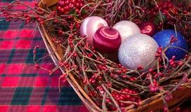 Una cesta de la Navidad en un mantel de la tela escocesa Foto de archivo libre de regalías