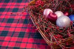 Una cesta de la Navidad en un mantel de la tela escocesa Imágenes de archivo libres de regalías