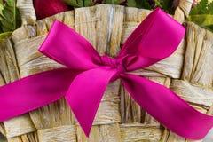 Una cesta de madera con la cinta rosada Fotografía de archivo