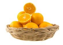 Una cesta de mimbre con las naranjas Foto de archivo