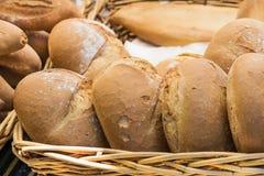 Una cesta de mimbre con varios pedazos de pan hecho a mano Foto de archivo