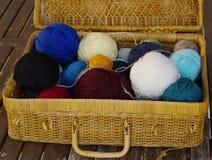 Una cesta de mimbre vieja con la tapa abierta, con las lanas restantes rueda Foto de archivo libre de regalías