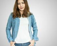 Una chaqueta de la mezclilla de la mujer que lleva asiática en el fondo blanco fotografía de archivo