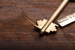 Una chiave della porta su un fondo di legno Fotografie Stock