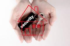 Una chiave di sicurezza dell'alloggio della tenuta della mano, concetto di sicurezza Fotografia Stock