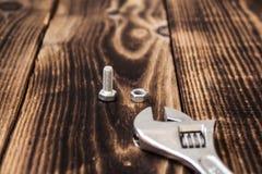 Una chiave e un bullone con il dado su fondo di legno immagine stock libera da diritti