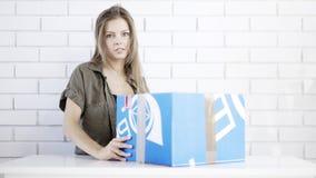 Una chica joven abre un regalo de la caja azul Imagen de archivo