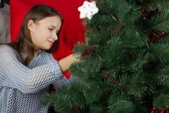 Una chica joven adorna un árbol de navidad Imagen de archivo