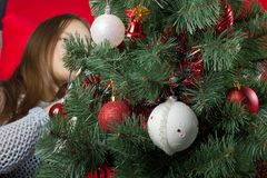 Una chica joven adorna un árbol de navidad Foto de archivo libre de regalías