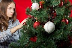 Una chica joven adorna un árbol de navidad Imágenes de archivo libres de regalías