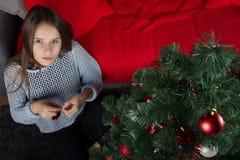 Una chica joven adorna un árbol de navidad Fotografía de archivo