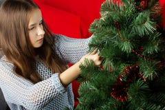 Una chica joven adorna un árbol de navidad Fotos de archivo