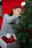 Una chica joven adorna un árbol de navidad Imagenes de archivo