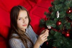 Una chica joven adorna un árbol de navidad Fotografía de archivo libre de regalías