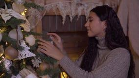 Una chica joven adorna un árbol de navidad con una bola hermosa que tiene un buen humor metrajes