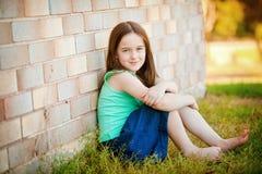 Una chica joven al aire libre que se inclina para arriba contra una pared de ladrillo. Foto de archivo