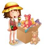 Una chica joven al lado de una caja de juguetes Foto de archivo libre de regalías