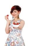 Una chica joven alcanza la taza de la cámara con las fresas Imagen de archivo libre de regalías