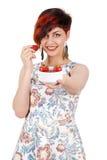 Una chica joven alcanza la taza de la cámara con las fresas Fotos de archivo libres de regalías