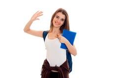 Una chica joven alegre en la camisa blanca aumentó una mano para arriba y mantiene la carpeta azul disponible Imagen de archivo libre de regalías