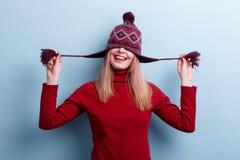 Una chica joven alegre que sonríe y que tira feliz del sombrero sobre ella ojos En un fondo azul imagenes de archivo