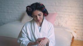 Una chica joven, ama de casa en los bigudíes, cuidando para la piel de las manos Retrato de la mujer del balneario de la belleza  almacen de video