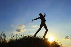 Una chica joven atractiva que salta en el aire en la puesta del sol Fotografía de archivo