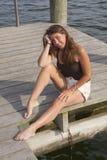 Una chica joven bonita que se sienta en un muelle de madera del barco fotos de archivo libres de regalías