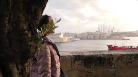 Una chica joven camina cerca del embarcadero con las naves por la tarde Paisaje hermoso, adolescente confiado acertado, turismo almacen de video