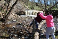 Una chica joven camina con su niño en la cascada imagen de archivo