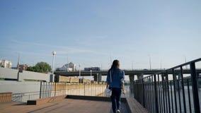 Una chica joven camina en el terraplén de la bahía de la ciudad metrajes