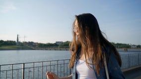 Una chica joven camina en el terraplén de la bahía de la ciudad almacen de video