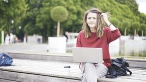 Una chica joven casual en el parque con un ordenador portátil Fotos de archivo libres de regalías