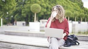 Una chica joven casual en el parque con un ordenador portátil Foto de archivo libre de regalías