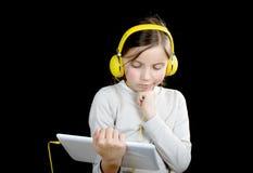 Una chica joven con auriculares amarillos y una tableta digital Fotos de archivo libres de regalías